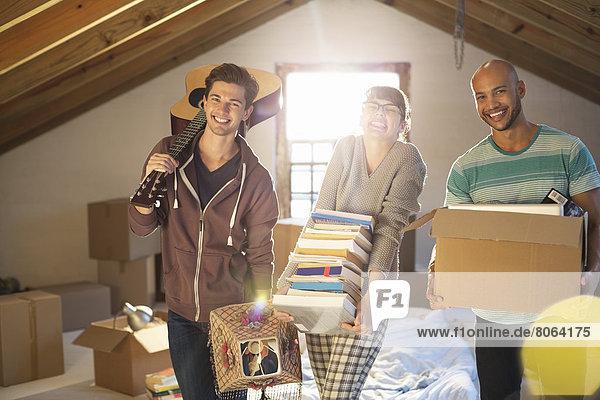 Freunde beim Auspacken von Kisten auf dem Dachboden
