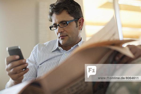 Mann mit Handy und Zeitung lesen