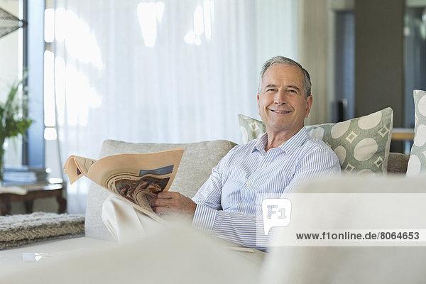 Älterer Mann liest Zeitung auf dem Sofa