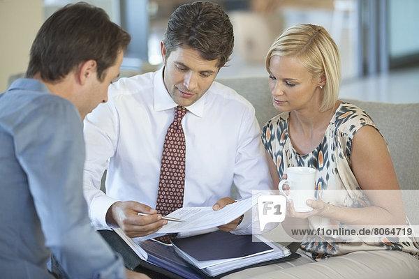 Finanzberater im Gespräch mit einem Paar auf dem Sofa