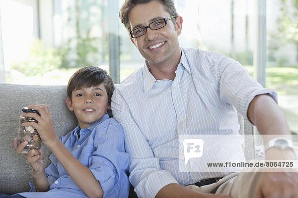 Vater und Sohn mit Wickeltopf auf dem Sofa