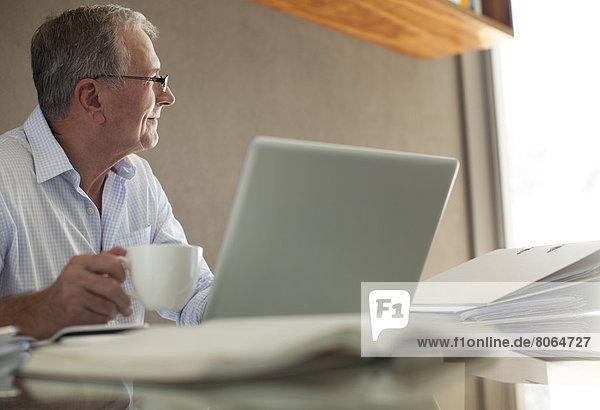 Geschäftsmann bei einer Tasse Kaffee am Laptop
