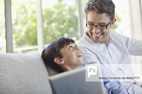 Vater und Sohn mit Tablet-Computer auf dem Sofa