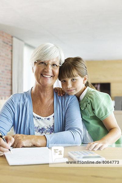Ältere Frau und Enkelin mit Taschenrechner