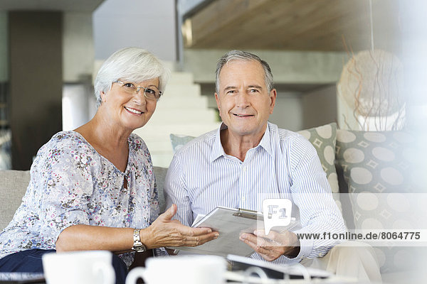 Älteres Paar liest Zwischenablage auf Sofa