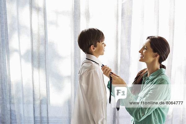 Mutter bindet die Krawatte des Sohnes am Fenster.