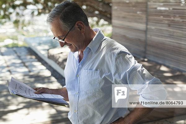 Geschäftsmann beim Lesen von Papieren im Freien