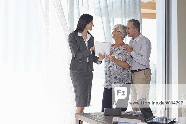 Finanzberater im Gespräch mit Ehepaar im Amt