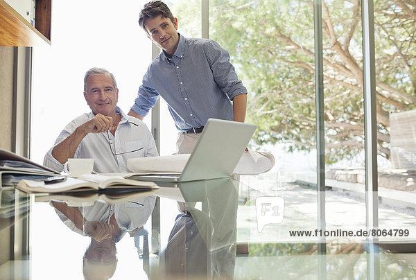 Geschäftsleute lächeln am Schreibtisch
