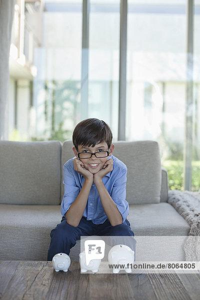 Junge untersucht Sparschweine auf dem Couchtisch