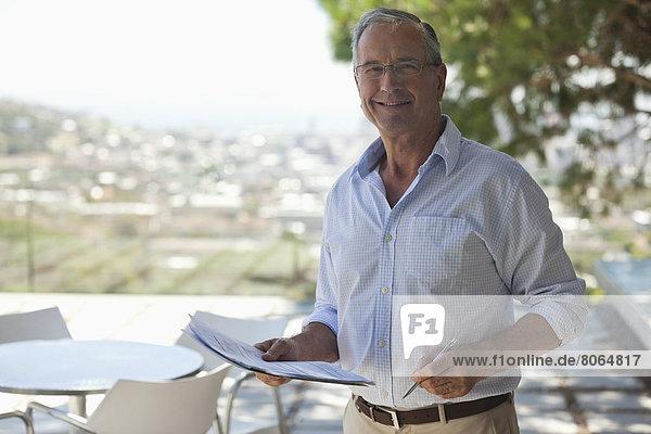 Älterer Mann beim Lesen von Papieren im Freien