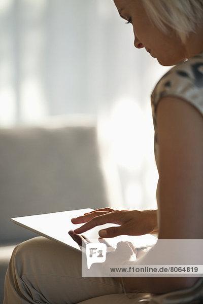 Frau mit Tablet-Computer auf dem Sofa