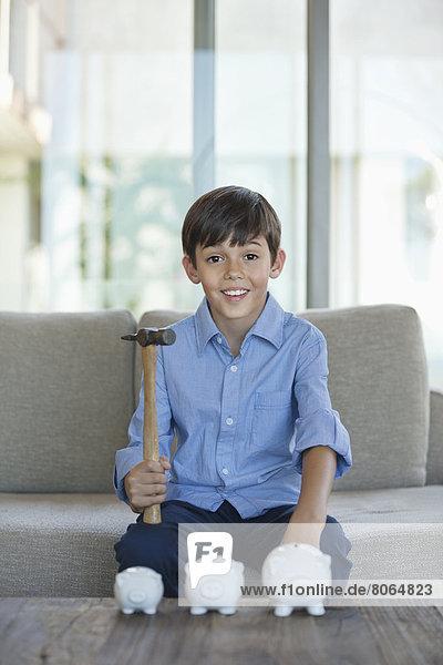 Junge hält Hammer zum Zerschlagen von Sparschweinen