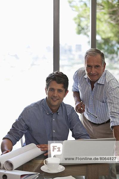 Älterer Mann und jüngerer Mann bei der Arbeit am Schreibtisch
