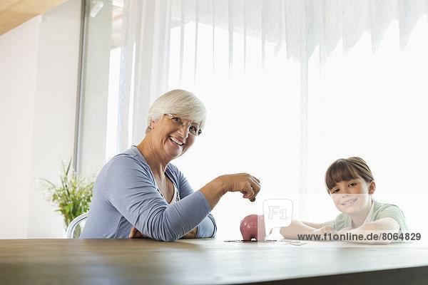 Ältere Frau und Enkelin beim Füllen des Sparschweins