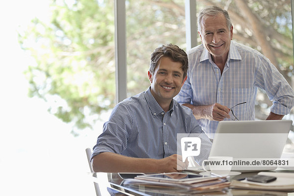 Älterer Mann und jüngerer Mann lächeln zusammen am Schreibtisch