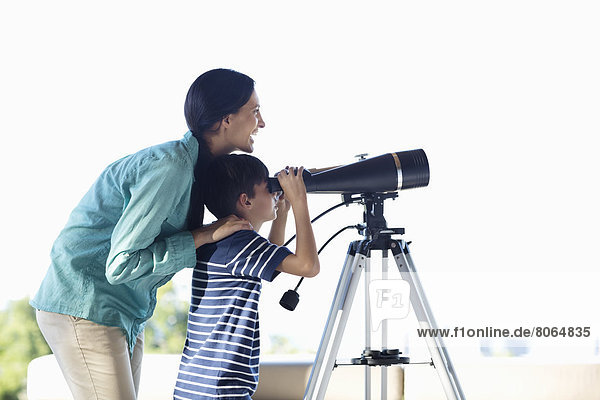 Mutter und Sohn mit Teleskop