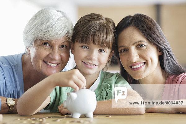 Drei Generationen von Frauen füllen Sparschwein