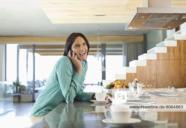 Frau spricht am Handy in der Küche
