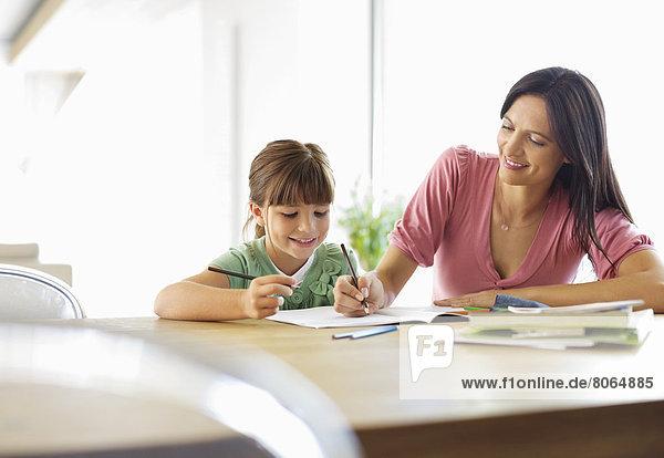 Mutter hilft Tochter bei den Hausaufgaben