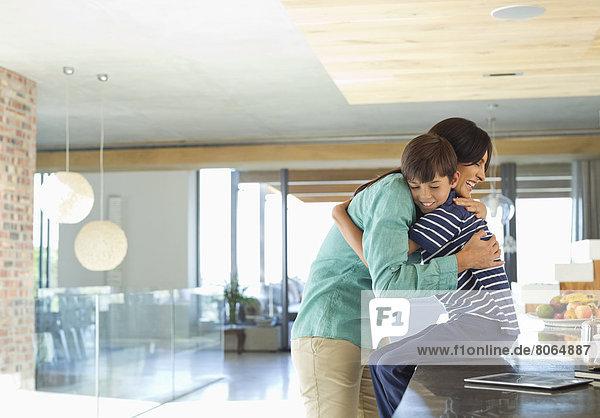 Mutter umarmt Sohn in der Küche