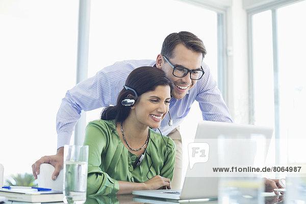 Geschäftsleute  die den Laptop gemeinsam am Schreibtisch benutzen