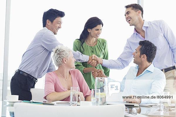 Geschäftsleute schütteln sich die Hand bei der Besprechung