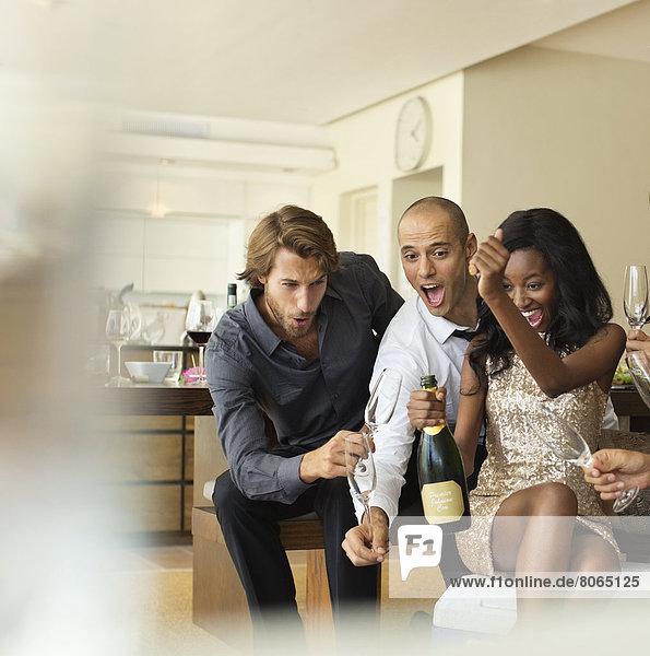 Freunde öffnen gemeinsam eine Flasche Champagner.