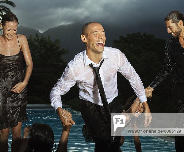Vollständig gekleidete Freunde beim Spielen im Schwimmbad