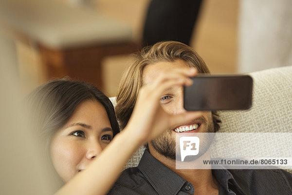 Paar mit Handy als Kamera zusammen auf dem Sofa