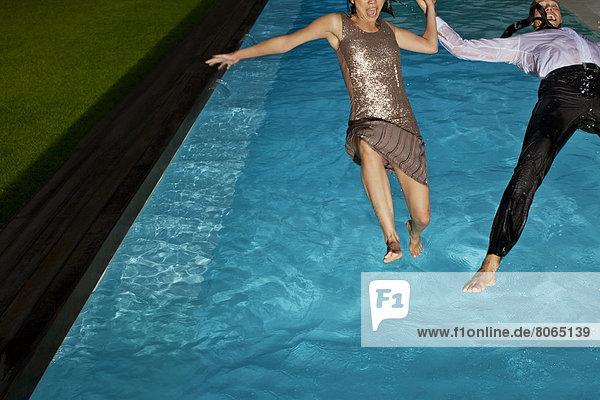 Vollständig gekleidetes Paar beim Sprung ins Schwimmbad