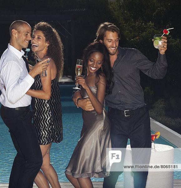 Freunde tanzen am Swimmingpool auf der Party