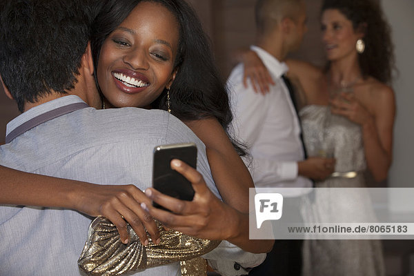 Frau mit Handy und umarmendem Freund