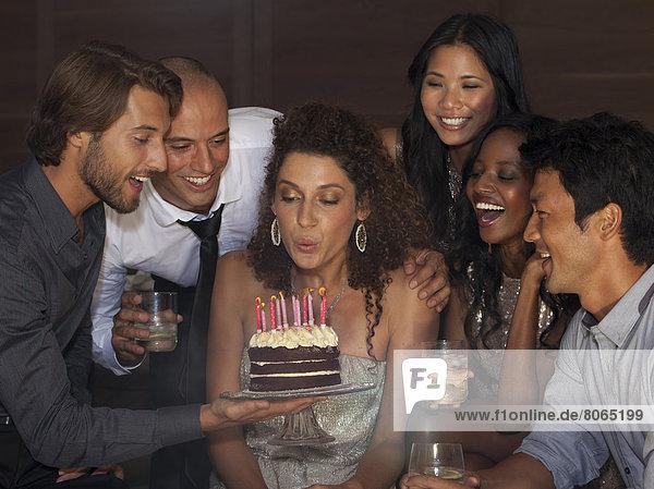 Frau beim Ausblasen von Geburtstagskerzen auf der Party