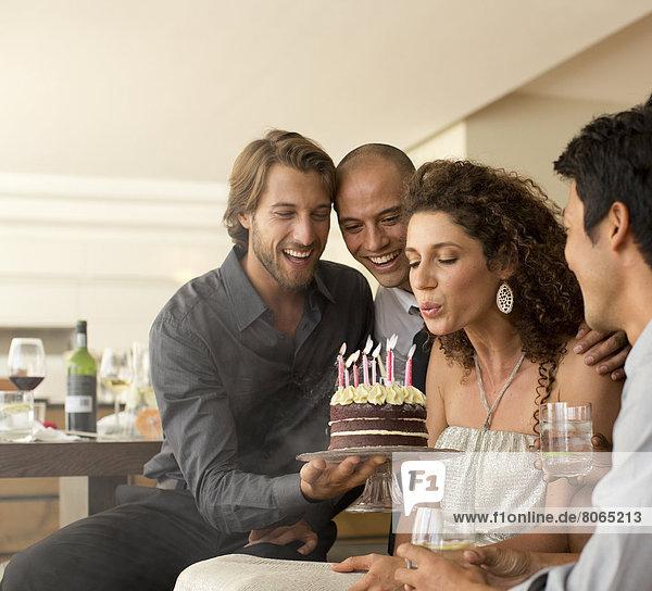 Frau bläst Geburtstagskerzen aus