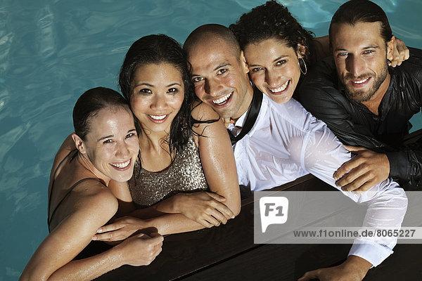 Vollständig gekleidete Freunde lächelnd im Schwimmbad