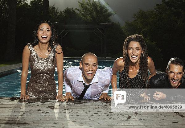 Vollständig gekleidete Freunde  die aus dem Schwimmbad klettern.