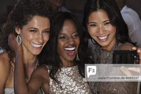 Frauen in Abendkleidern beim gemeinsamen Fotografieren