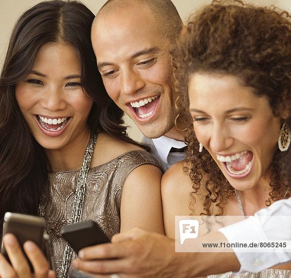 Freunde  die zusammen Handys benutzen