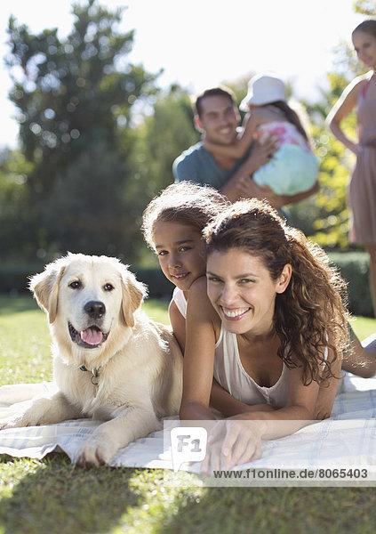 Mutter  Tochter und Hund im Gras liegend