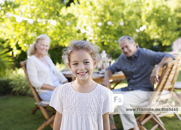 Girl smiling in backyard with grandparents