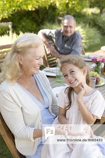 Ältere Frau sitzend mit Enkelin im Freien