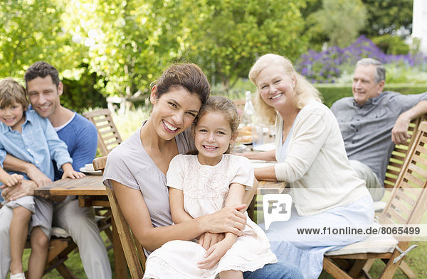 Family smiling at table outdoors