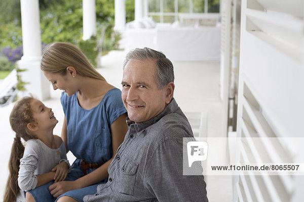 Älterer Mann lächelt auf der Veranda