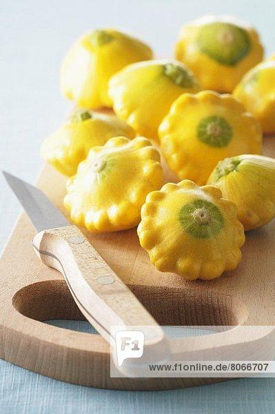 Mehrere gelbe Patissons auf Schneidebrett mit Messer Mehrere gelbe Patissons auf Schneidebrett mit Messer
