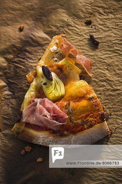 Ein Stück Pizza mit Pancetta  Artischocken und schwarzen Oliven
