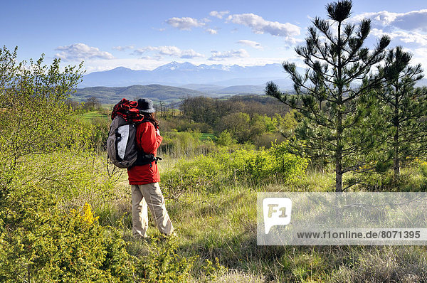 Woman with a backpack on the Way of St James between Fanjeaux  Aude department (11) and Mirepoix  Ariege department (09). Woman in the countryside looking at the landscape in the Pre-Pyrenees