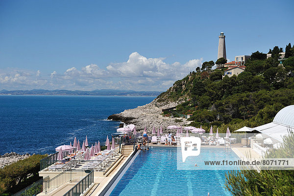 Saint-Jean-Cap-Ferrat (06). June 2010. The coast between Nice and Monaco viewed from the Grand Hotel of Cape Ferrat. Sunshades  deckchairs  swimming pool  lighthouse