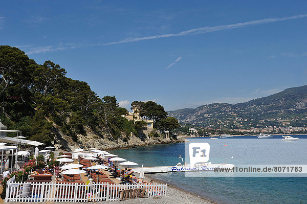 'Saint-Jean-Cap-Ferrat (06) June 2010. Paloma private beach and ''Paloma Beach'' restaurant facing the bay of Beaulieu-sur-Mer. Sunshades  deckchairs. View of the coasr. Launches lying at anchor'