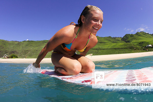 Young and tanned surfer with blond hair  on her surfboard in the blue water of the ocean  wearing a colored Roxy swimsuit
